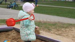 Lilla flickan spelar i en sandlåda med en röd spatel, närbild stock video