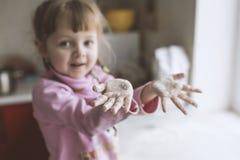 Lilla flickan spelar i köket, händer i mjöl Royaltyfri Foto