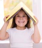 Lilla flickan spelar med boken Arkivbilder