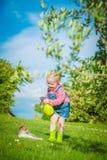 Lilla flickan spelar med en katt på ett grönt gräs Royaltyfri Bild