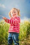 Lilla flickan spelar med mellan gröna korn på bygd Arkivfoton
