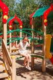 Lilla flickan spelar på lekplatsen Arkivbild