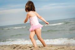 Lilla flickan spelar på sanden på stranden royaltyfria foton