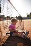 Lilla flickan spelar tennis Arkivfoto