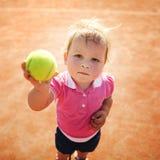 Lilla flickan spelar tennis Arkivbild