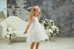 Lilla flickan spining i den vita lyxiga klänningen arkivbild