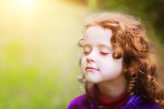 Lilla flickan stängde henne ögon och andas den nya luften i PA Arkivfoto