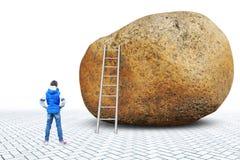 Lilla flickan står framme av en enorm sten nära som där är en stege arkivfoton