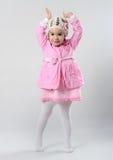 Lilla flickan står på hennes tåspetsarna och lyfter henne händer fotografering för bildbyråer
