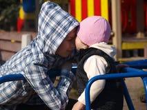 Lilla flickan sträcker för att kyssa hennes tonåriga broder, medan sitta på karusellen fotografering för bildbyråer