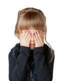 Lilla flickan täcker hennes framsida med händer arkivfoto
