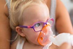 Lilla flickan tar inandningterapi Royaltyfri Foto