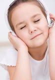 Lilla flickan tycker om musik genom att använda hörlurar Arkivbild