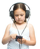 Lilla flickan tycker om musik genom att använda hörlurar Arkivbilder