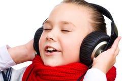 Lilla flickan tycker om musik genom att använda hörlurar Arkivfoto