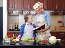 Lilla flickan undervisar hennes moder att laga mat royaltyfria bilder