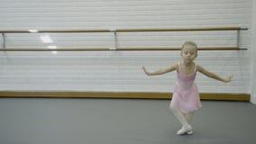 Lilla flickan utför dansförehavanden i balettskola stock video