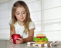 Lilla flickan väljer mellan äpplet och hamburgaren Sjuklig nutriti Royaltyfri Foto
