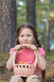 Lilla flickan väljer upp champinjoner i skog Arkivbilder