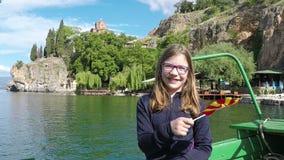 Lilla flickan vinkar med en Macedonian flagga på Ohrid sjön arkivfilmer