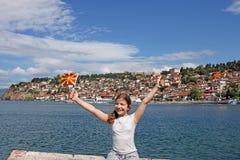 Lilla flickan vinkar med en Macedonian flagga på sjön Ohrid Arkivbilder