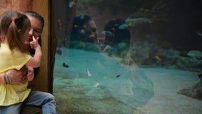 Lilla flickan visar Admiringly hennes moder något i stort akvarium på Oceanarium De har mycket gyckel på lager videofilmer