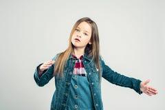 Lilla flickan visar en robot barnet poserar i studion och gör förehavanden med hans händer och fot fashion ungar arkivbild