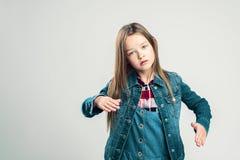 Lilla flickan visar en robot barnet poserar i studion och gör förehavanden med hans händer och fot fashion ungar royaltyfria foton