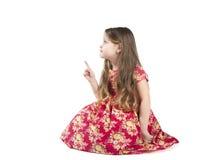 Lilla flickan visar ett finger till sidan Arkivbild