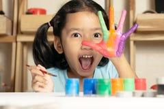 Lilla flickan visar målad färg arkivbild