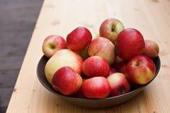 Lilla och stora äpplen i en bunke Arkivfoto