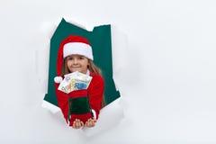 Lilla santa som ger dig pengar för semesterperioden Arkivfoto