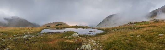 Lilla Tarn med dimma i berg på solnedgången Fotografering för Bildbyråer