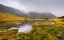 Lilla Tarn med vaggar i dimmiga berg Fotografering för Bildbyråer