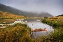 Lilla Tarn med vaggar i dimmiga berg Arkivbilder