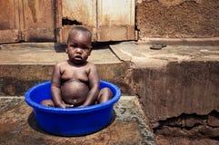 Lille barn som badar i en by i Uganda arkivbilder