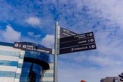 Lille, França - 3 de junho de 2015: Sinais que mostram sentidos aos lugar turísticos diferentes para pedestres, prédio de escritó Fotografia de Stock Royalty Free