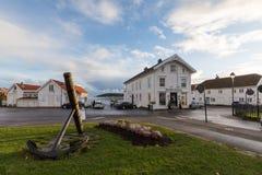 Lillesand, Noruega - 10 de noviembre de 2017: Ancla en un parque, con la tienda y el restaurante en el fondo Océano y cielo Fotos de archivo libres de regalías