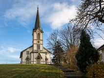 Lillesand, Noruega - 10 de noviembre de 2017: La iglesia en Lillesand Front View Cielo azul, nubes, hierba verde y escalera Fotografía de archivo libre de regalías