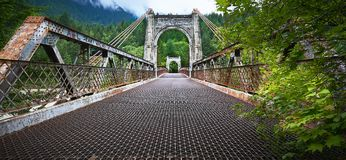 Rusty metal suspension bridge over the Fraser river near Lillooet, British Columbia, Canada royalty free stock photos