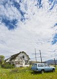 Settlement of few houses and an old car in front, near a highway in British Columbia, Canada stock photography