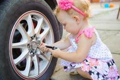 Lillte barn som leker i auto mekaniker Arkivbilder