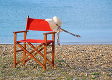 Summer on the beach deckchair hat. Photo of a ladies summer hat on a deck chair with a gentle sea breeze blowing the ribbons...while lilly relaxes somewhere on Stock Images