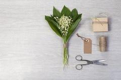 Lilly dolina liści i kwiatów bukiet z pudełkowatym prezentem na drewnianym tle kosmos kopii Obrazy Royalty Free