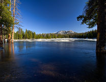 Lilly Lake in the Spring covered with ice with trees on the side Stock Photo