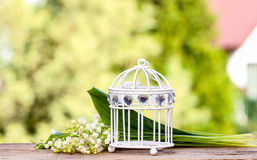 Lilly of the valley flowers and decorative vintage birdcage Royalty Free Stock Photo