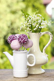 Lilly of the valley flowers and pastel cake pops Stock Photography