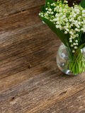 Lilly of valley on wood. Lilly of the valley flowers in glass on wooden table close up Stock Photo