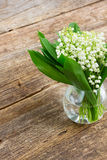 Lilly of valley on wood. Lilly of valley in glass on wooden table close up Stock Photo
