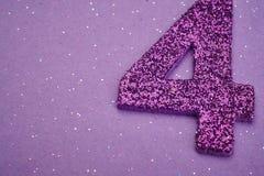 Lilor för nummer fyra färgar över en purpurfärgad bakgrund årsdagen Royaltyfri Foto